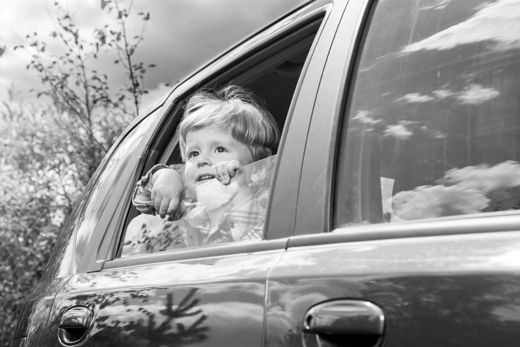 child sitting in car and looking out window